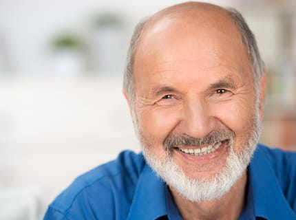 smiling man with implant supported dentures