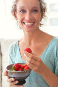 Close up portrait of a mature healthy woman joyfully smiling and eating red strawberries at home while relaxing on a white sofa in a home living room, indoors. Healthy eating and well being lifestyle, interior.